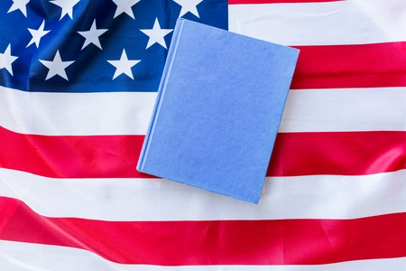 nationalism: american independence day, patriotism and nationalism concept - close up of american flag and book Stock Photo
