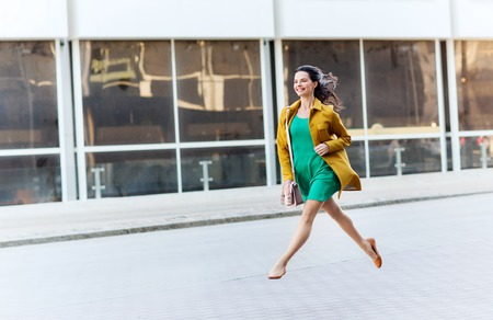 haste: fashion and people concept - happy young woman or teenage girl running and jumping high on city street Stock Photo