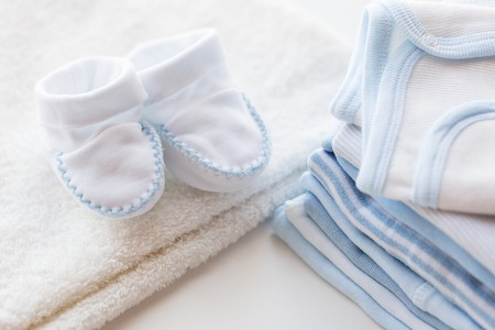 bootees: clothing, babyhood, motherhood and object concept - close up of white baby bootees with pile of clothes for newborn boy