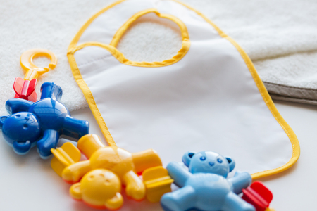 babyhood: babyhood, childhood, accessory and object concept - close up of baby rattle and bib for newborn boy on towel