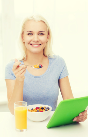 good food: healthy eating, dieting and people concept - smiling young woman with tablet pc computer eating breakfast at home