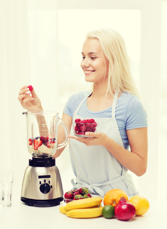 blender: healthy eating, cooking, vegetarian food, dieting and people concept - smiling young woman putting fruits and berries for fruit shake to blender shaker at home