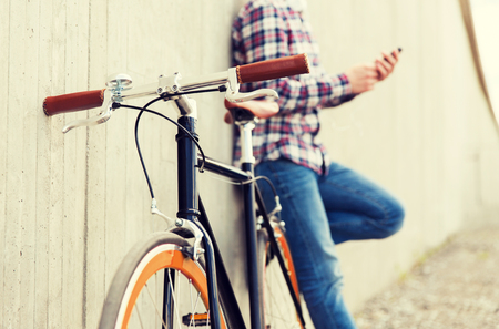 fixed: people, transport, leisure and lifestyle - close up of hipster fixed gear bike and man on city street