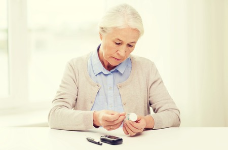 home health care: medicine, age, diabetes, health care and people concept - senior woman with glucometer and test stripes checking blood sugar level at home