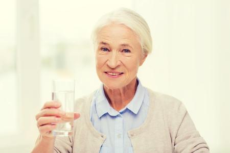 tomando agua: la edad, la salud y las personas concepto - mujer feliz altos con un vaso de agua en el hogar Foto de archivo