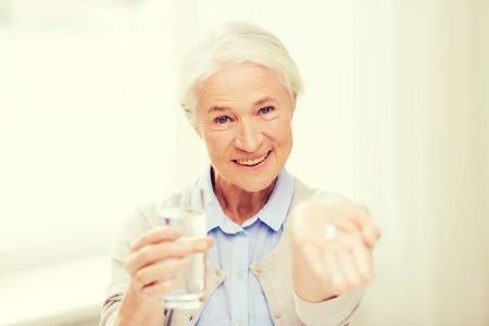 home health care: age, medicine, health care and people concept - happy senior woman with pills and glass of water at home