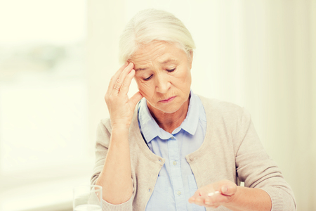 home health care: age, medicine, health care and people concept - senior woman with pills and glass of water at home Stock Photo