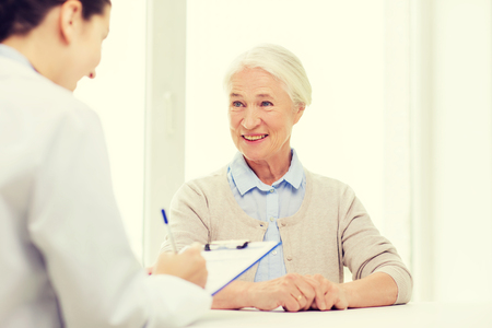 medicine, age, health care and people concept - doctor with clipboard writing prescription for senior woman at hospital Stock Photo