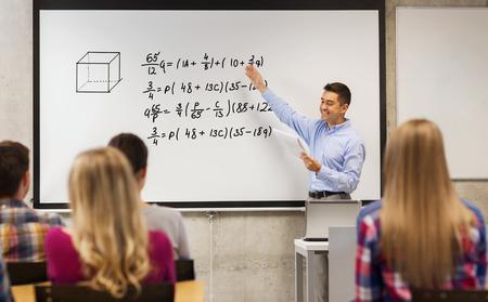 geometria: la educación, la escuela secundaria, las matemáticas y el concepto de la gente - profesor sonriente con la libreta de pie delante de los estudiantes y que muestra igualdades matemáticas en la pizarra en el aula