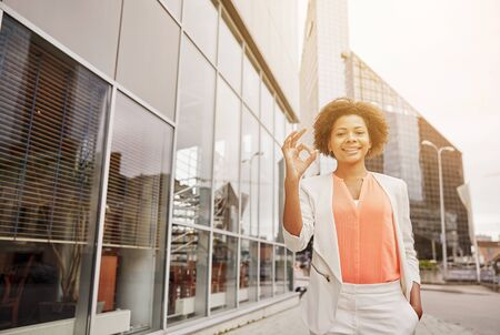 business, gesture and people concept - young smiling african american businesswoman in city showing ok hand sign