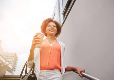 down the stairs: negocios y concepto de la gente - joven sonriente africano americano de negocios con la taza de café bajando escaleras en paso subterráneo de la ciudad