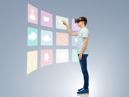 mediated: 3d technology, virtual reality, entertainment, cyberspace and people concept - happy young man with virtual reality headset or 3d glasses playing game and touching screen with menu icons