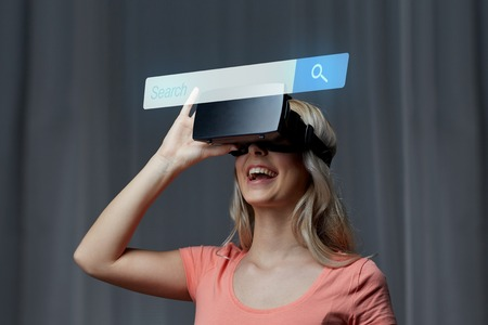 internet browser: technology, virtual reality, cyberspace, entertainment and people concept - happy young woman with virtual reality headset or 3d glasses at home looking at internet browser search bar projection Stock Photo