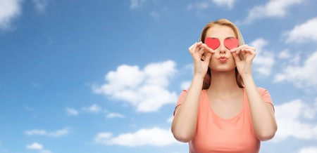 romance sky: love, romance, valentines day and people concept - smiling young woman or teenage girl with red heart shapes on eyes over blue sky and clouds background