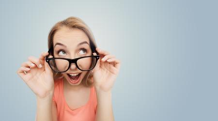 La visión, la educación y el concepto de la gente - Feliz sonriente joven mujer o niña adolescente anteojos sobre fondo gris Foto de archivo - 62368819