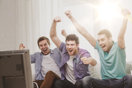 friendship, sports and entertainment concept - happy male friends with vuvuzela watching sports on tv