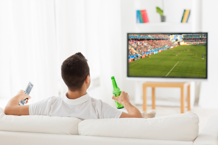 leisure, technology, mass media and people concept - man watching football or soccer game on tv and drinking beer from bottle at home from back