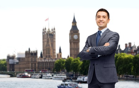 kingdom: business trip, people and office concept - happy smiling businessman in dark grey suit over london city background