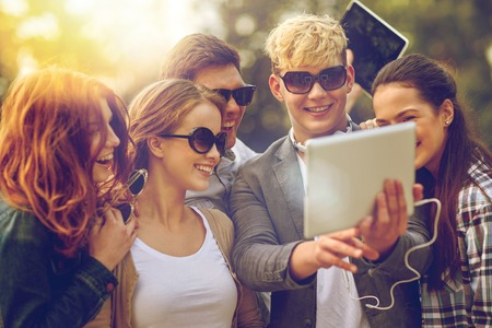 school teens: summer, technology, education and teenage concept - group of happy students or teenagers with tablet pc computer taking selfie
