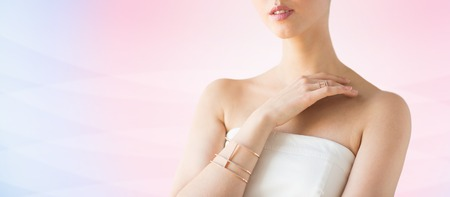 bride bangle: glamour, beauty, jewelry and luxury concept - close up of beautiful woman with golden ring and bracelet over pink background