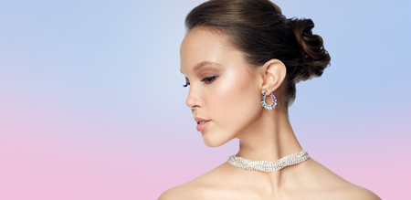 jewel: beauty, jewelry, accessories, people and luxury concept - close up of beautiful asian woman face with earring over rose quartz and serenity gradient background Stock Photo