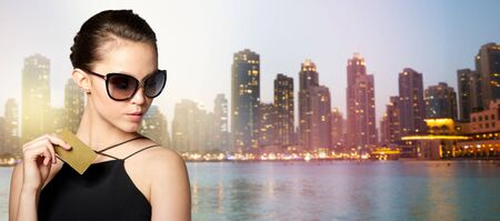 shopping card: shopping, finances, fashion, people and luxury concept - beautiful young woman in elegant black sunglasses with credit card over dubai night city lights street background