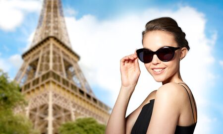 eyewear fashion: accessories, eyewear, fashion, people and luxury concept - beautiful young woman in elegant black sunglasses over paris eiffel tower background