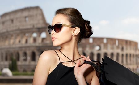 Verkoop, tour, mode, mensen en luxe concept - gelukkige mooie jonge vrouw in zwarte zonnebril met boodschappentassen over coliseum achtergrond