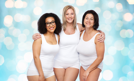 light blue lingerie: friendship, beauty, body positive and people concept - group of happy plus size women in white underwear over blue holidays lights background