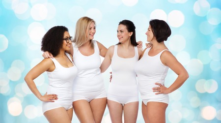 light blue lingerie: friendship, beauty, body positive and people concept - group of happy women different in white underwear over blue holidays lights background Stock Photo