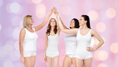 mid age: gesture, friendship, beauty, body positive and people concept - group of happy different women in white underwear making high five over rose quartz and serenity lights background