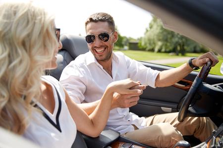 Autoreise, Reise, Datierung, Paar und Leutekonzept - glücklicher Mann und Frau, die draußen in Cabrioletauto fährt