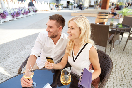 date, people, payment and finances concept - happy couple with wallet, credit card and wine glasses paying bill at restaurant