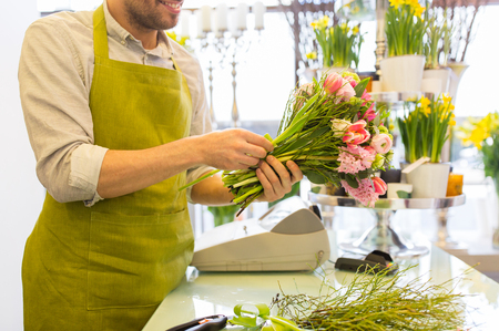people, business, sale and floristry concept - close up of happy smiling florist man making bunch at flower shop Imagens