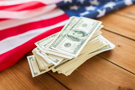 nationalism: budget, finance and nationalism concept - close up of american flag and dollar cash money on wood