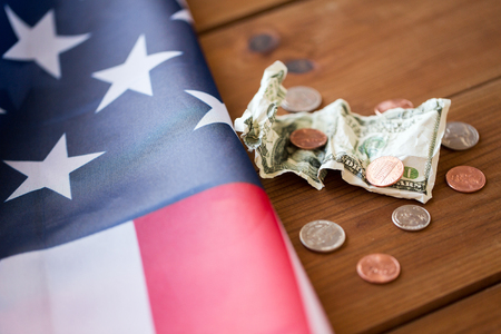 budget crisis: budget, money, finance, financial crisis and nationalism concept - close up of american flag and cent coins with crumpled dollar banknote on wood Stock Photo