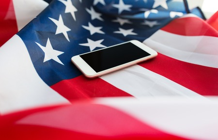 nationalism: technology, american independence day, patriotism and nationalism concept - close up of smartphone computer on american flag