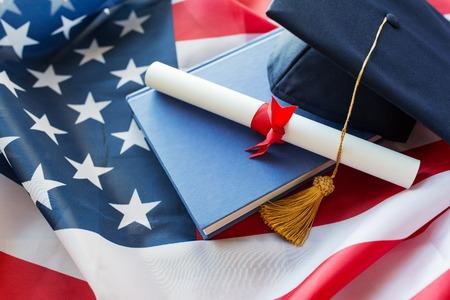 l'éducation, l'obtention du diplôme, le patriotisme et le nationalisme concept - gros plan de chapeau de baccalauréat et diplôme sur le drapeau américain Banque d'images