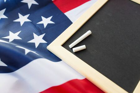 nationalism: education, election, patriotism and nationalism concept - close up of blank school blackboard and chalk on american flag