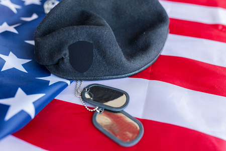 conscription: military forces, service, patriotism and nationalism concept - close up of american flag, soldiers badges and paratrooper hat Stock Photo