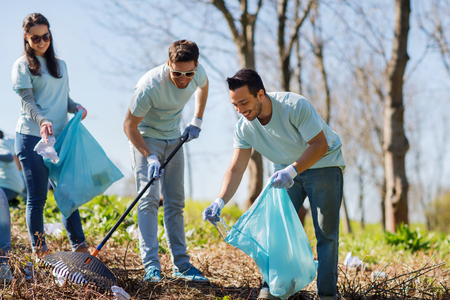 volunteering, charity, cleaning, people and ecology concept - group of happy volunteers with garbage bags cleaning area in park Imagens - 62372762