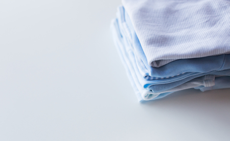 clean clothes: clothing, babyhood, motherhood and object concept - close up of pile of baby clothes for newborn boy folded on table