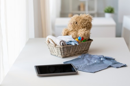 babyhood: babyhood, motherhood, clothing, technology and object concept - close up of baby clothes and toys for newborn boy in basket with tablet pc computer at home