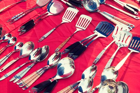 multiple objects: tableware and kitchenware concept - spoons and spatulas sale at street market