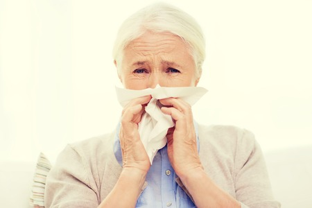 home health care: health care, flu, hygiene, age and people concept - sick senior woman blowing nose to paper napkin at home Stock Photo
