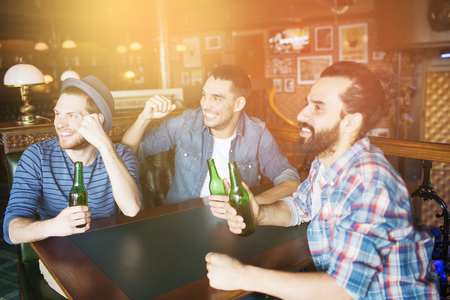 bottled beer: people, leisure, friendship and bachelor party concept - happy male friends drinking bottled beer and raised hands rooting for football match at bar or pub
