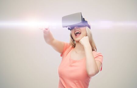 game over: 3d technology, virtual reality, entertainment and people concept - happy young woman with virtual reality headset or 3d glasses playing game and fighting over gray background and laser light Stock Photo