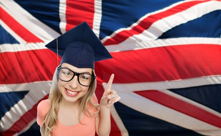 british girl: people, graduation and national education concept - smiling young student woman in mortarboard and eyeglasses pointing finger up over english flag Stock Photo