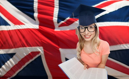the encyclopedia: people, national education, knowledge and graduation concept - smiling young student woman in mortarboard and eyeglasses with encyclopedia book over english flag Stock Photo