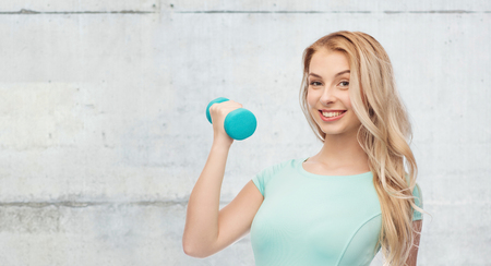 fitness, sport, exercising and people concept - smiling beautiful sporty woman with dumbbell over gray concrete wall background